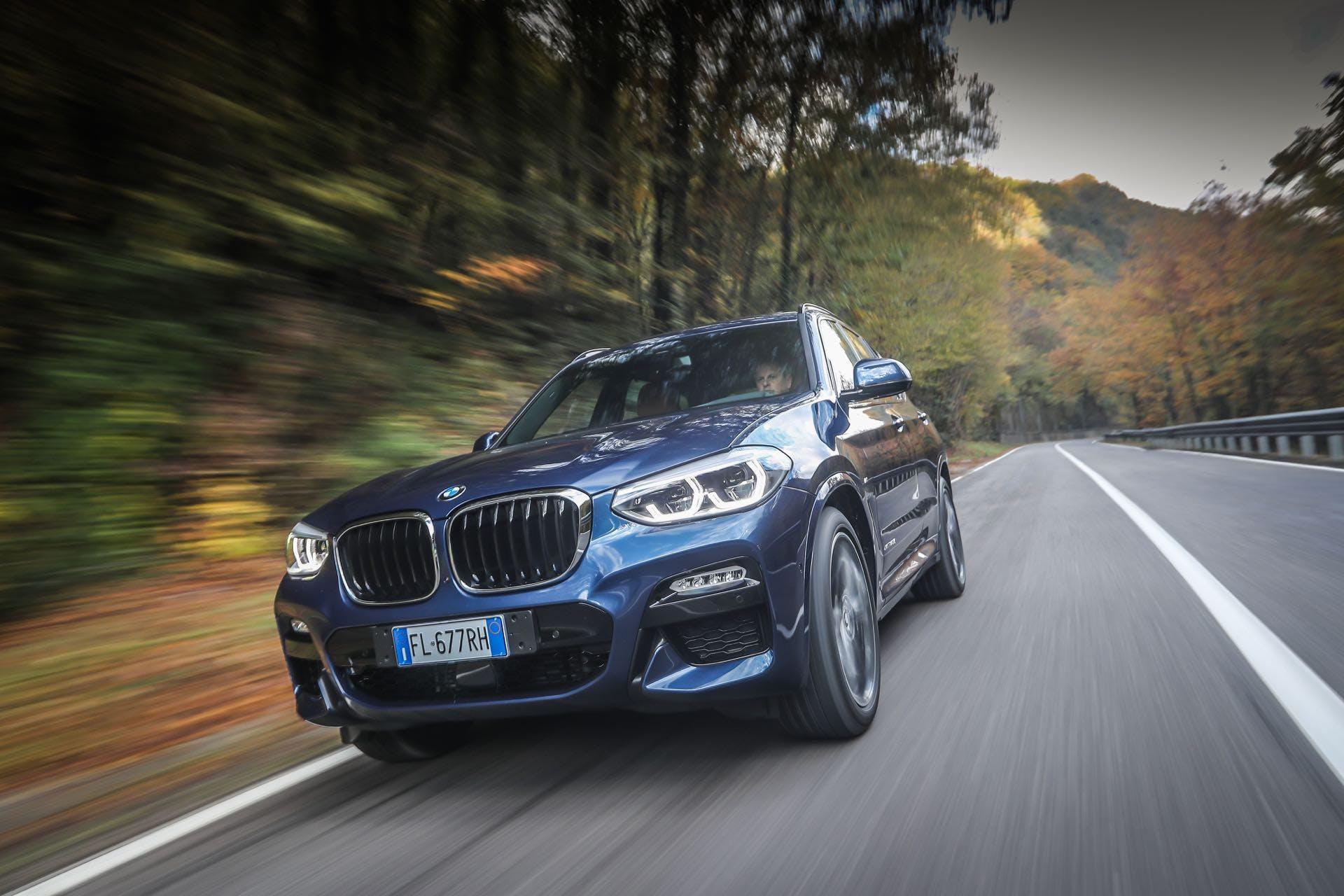 BMW X3 color blu guidata su strada vista frontalmente