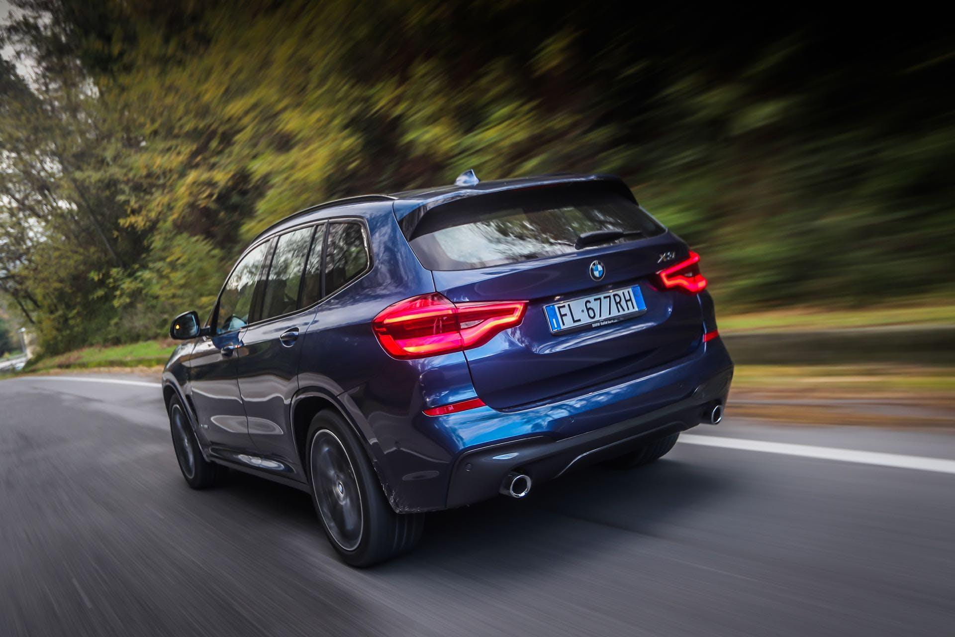 BMW X3 color blu guidata su strada vista da dietro