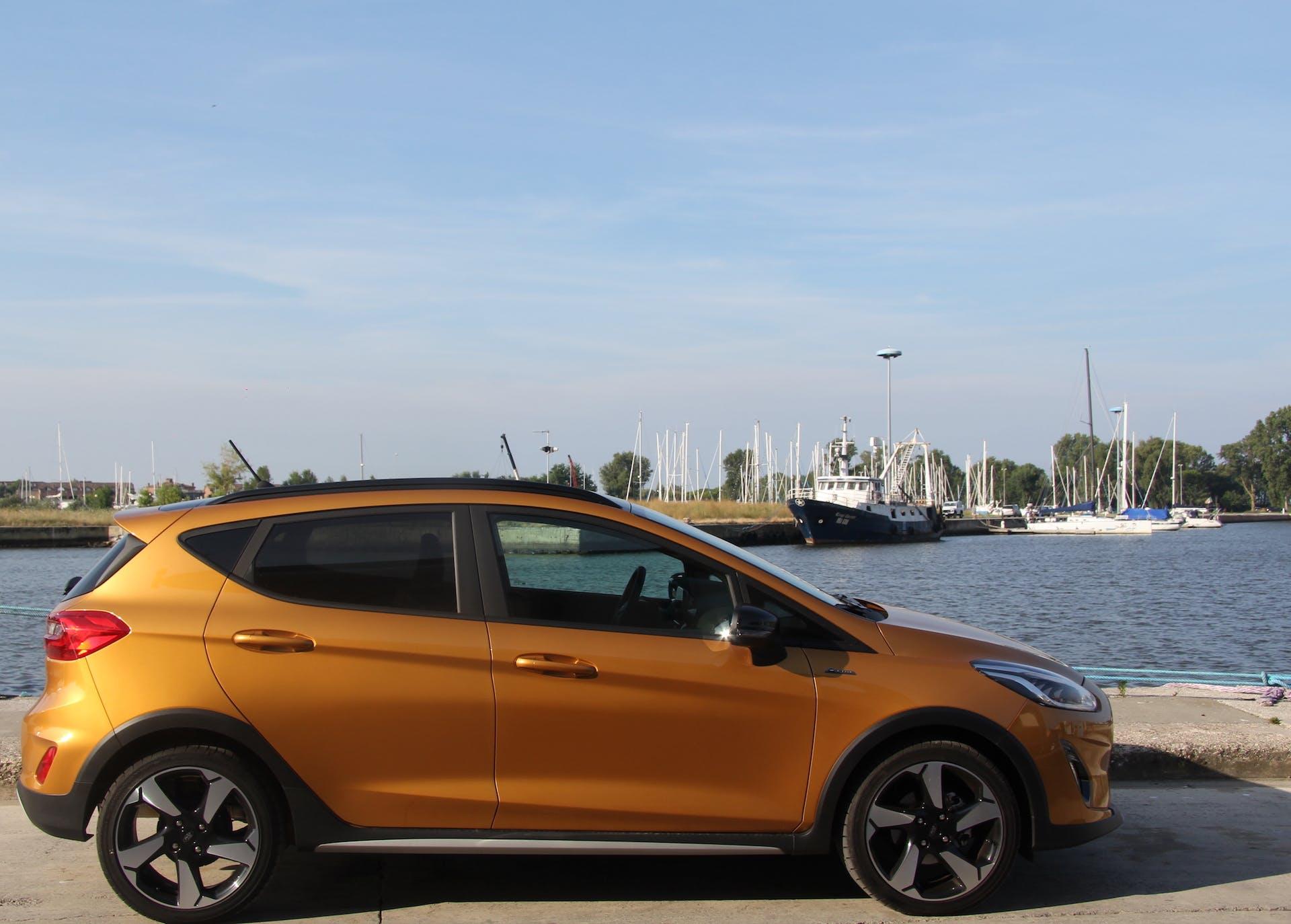 Ford Fiesta Active color terra bruciata vista laterale con un porto sullo sfondo