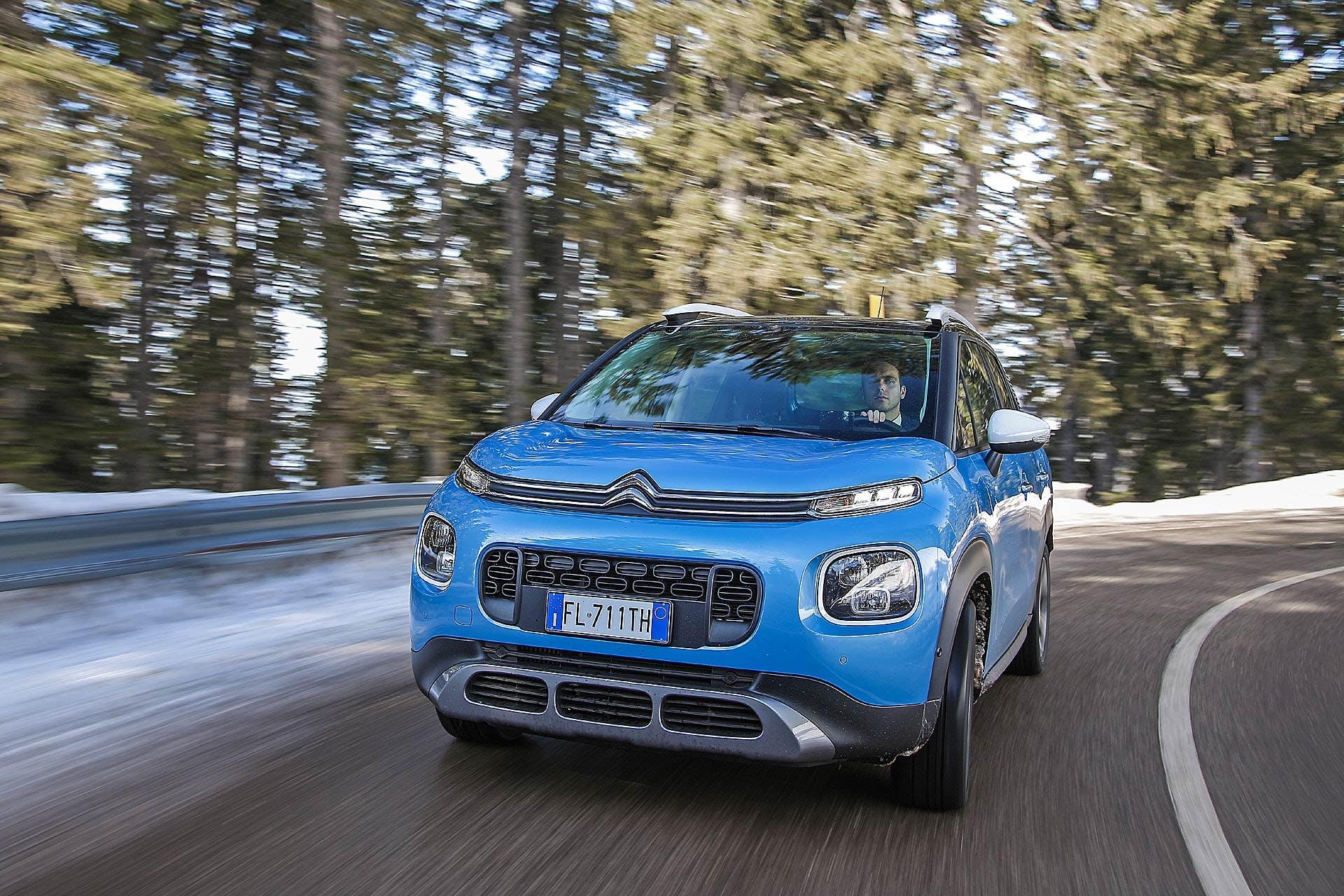 Citroën C3 Aircross azzurra impegnata in curva asfaltata di montagna tra pini e neve