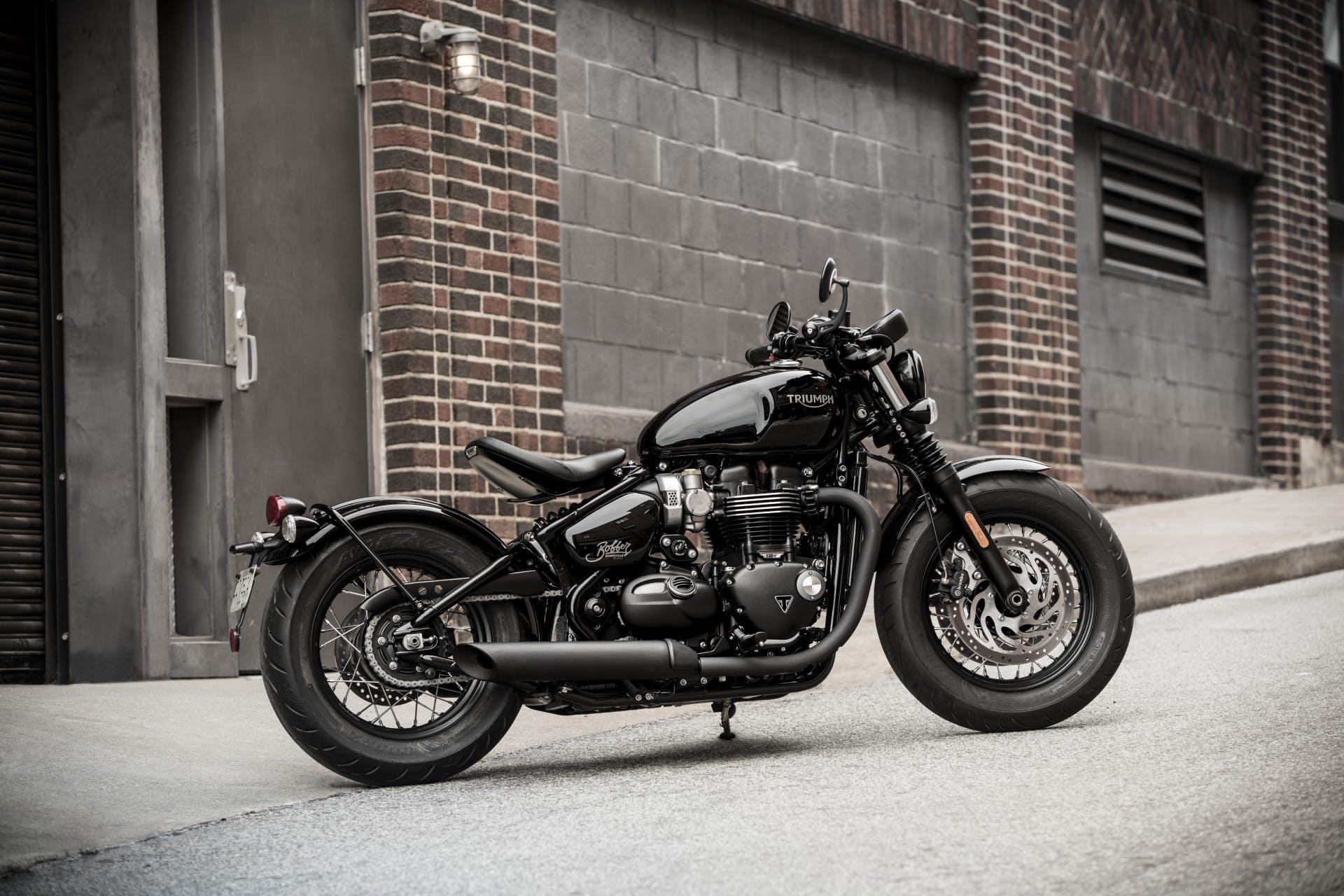 moto triumph bonneville bobber black, vista laterale ambientata