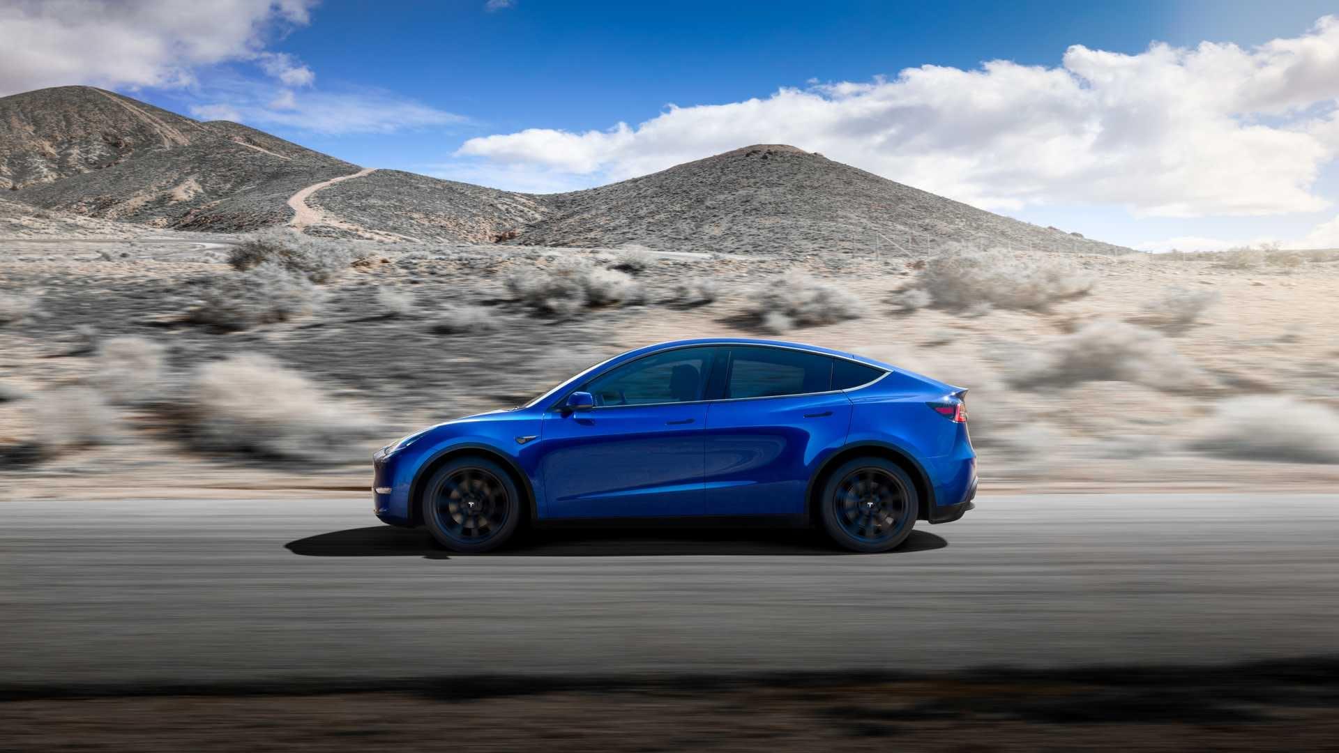 Tesla Model Y auto blu vista laterale dinamica su strada sfondo paesaggio