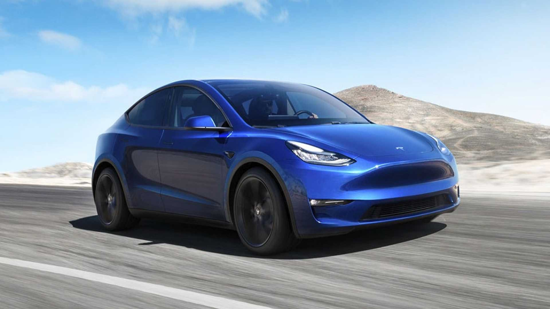 Tesla Model Y auto blu vista tre quarti dinamica su strada sfondo paesaggio