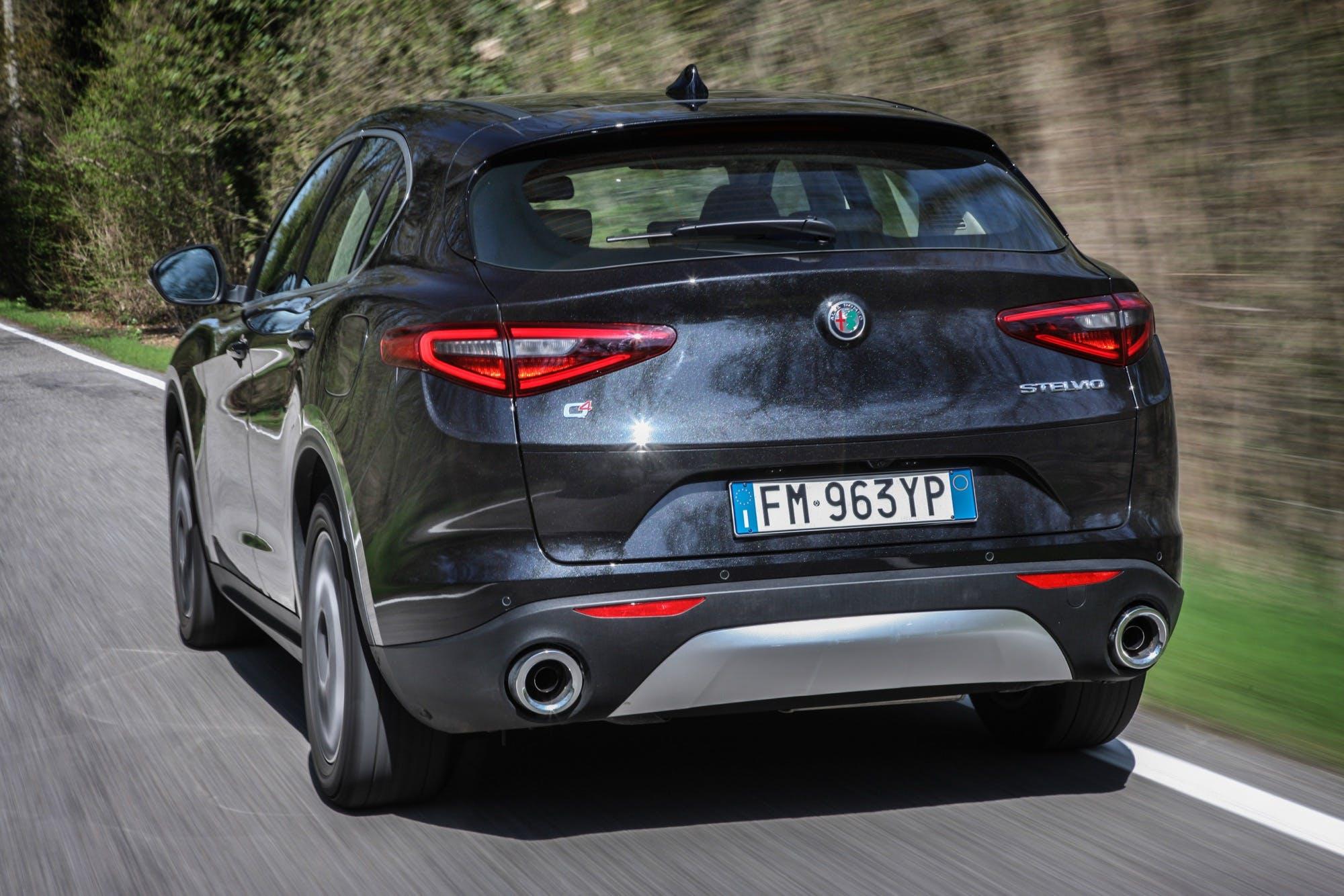 Alfa Romeo Stelvio posteriore in movimento su strada nera