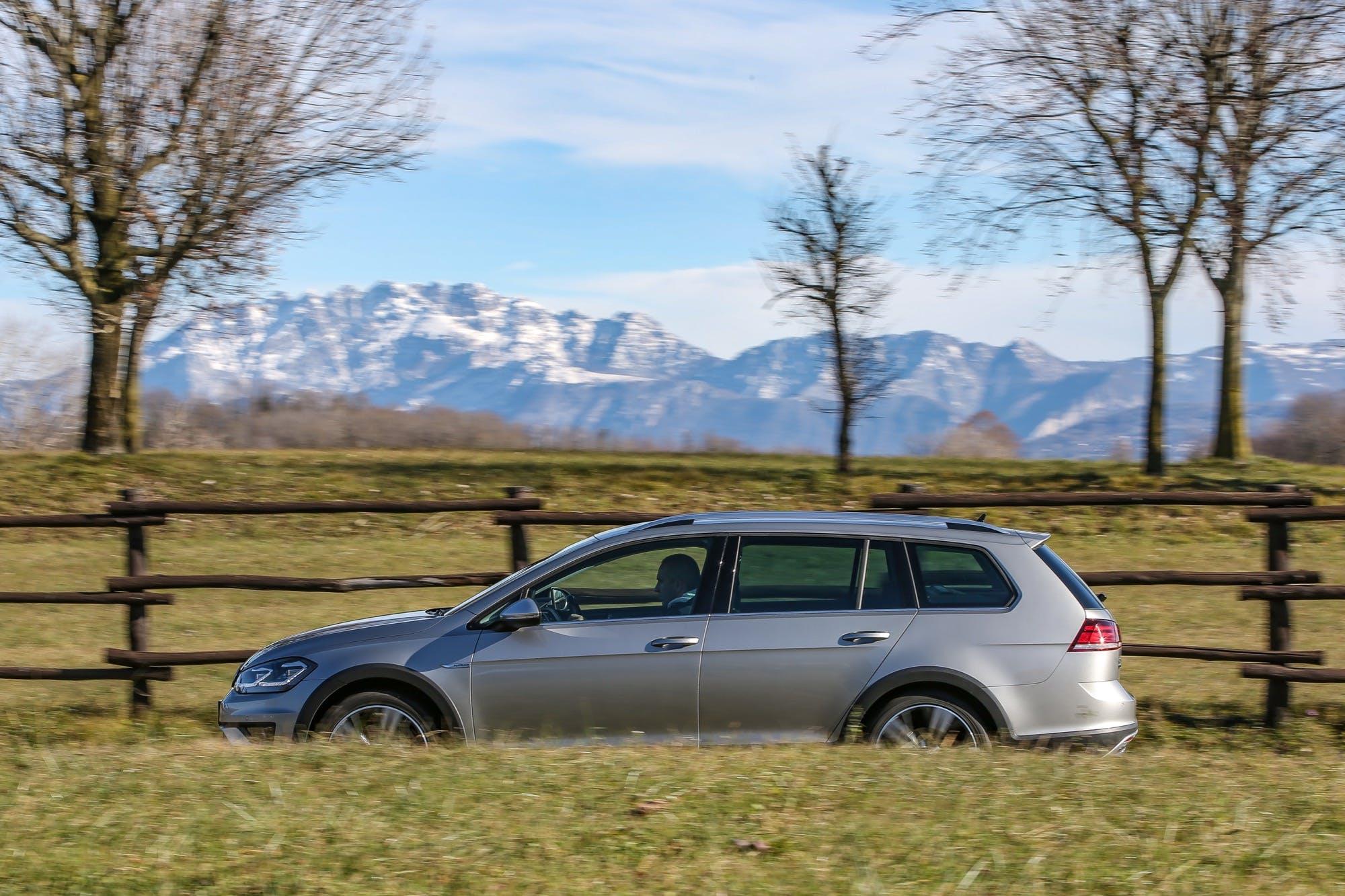 Volkswagen Golf Alltrack laterale in movimento grigia con dietro montagne su strada