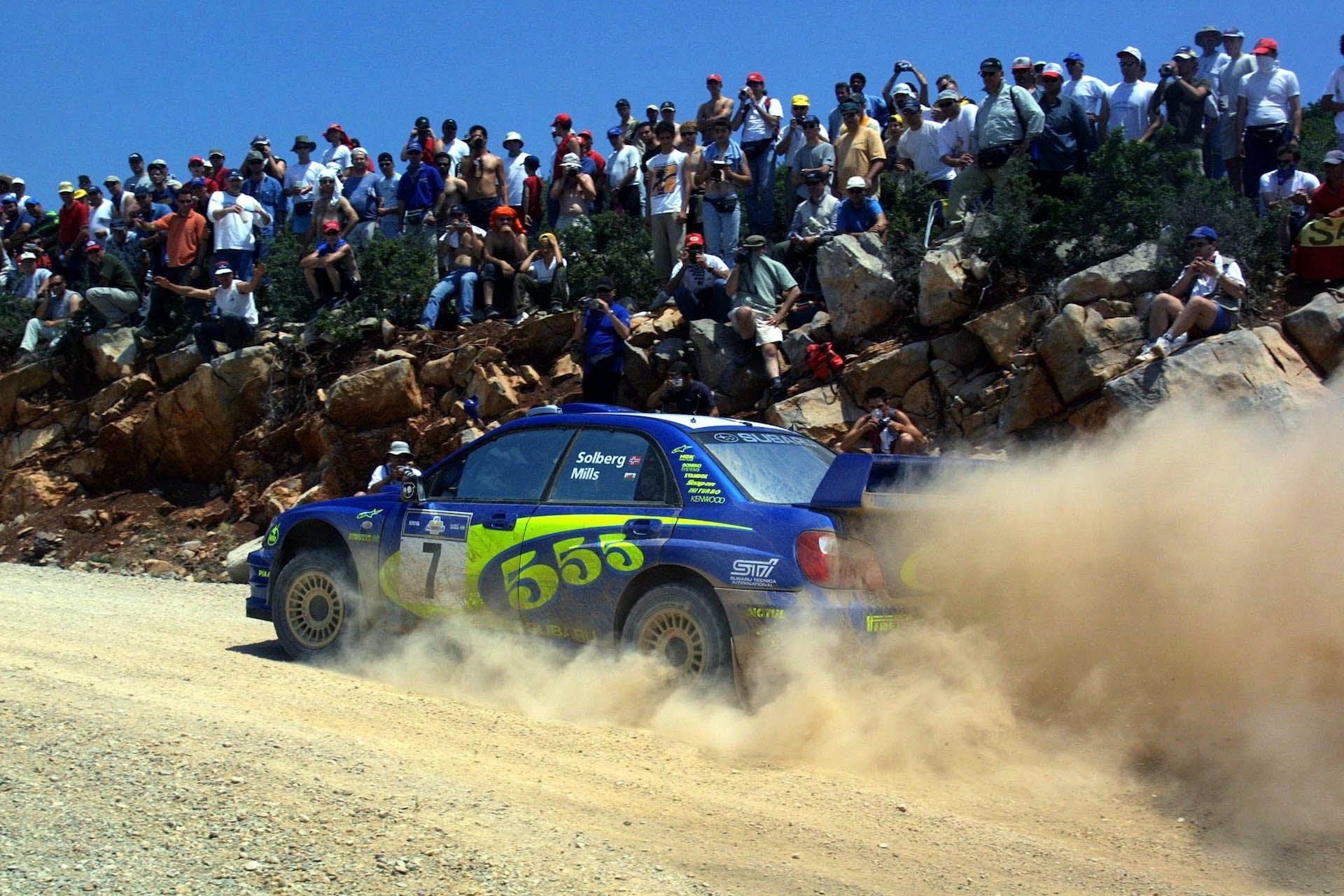 Subaru Impreza rally su sabbia laterale in movimento con spettatori blu
