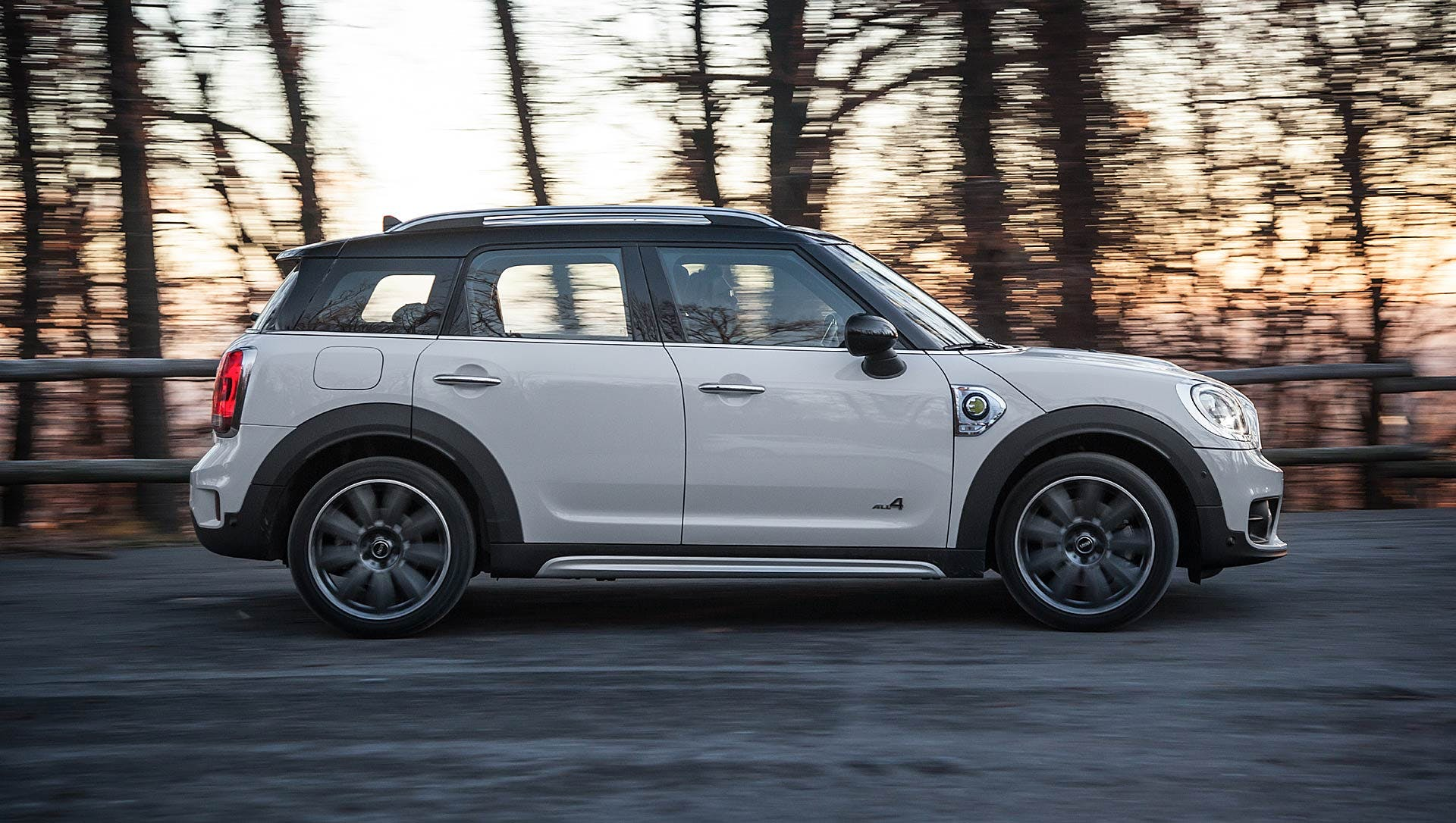 Mini Cooper Countryman SE bianca in curva con sfondo di alberi e tramonto