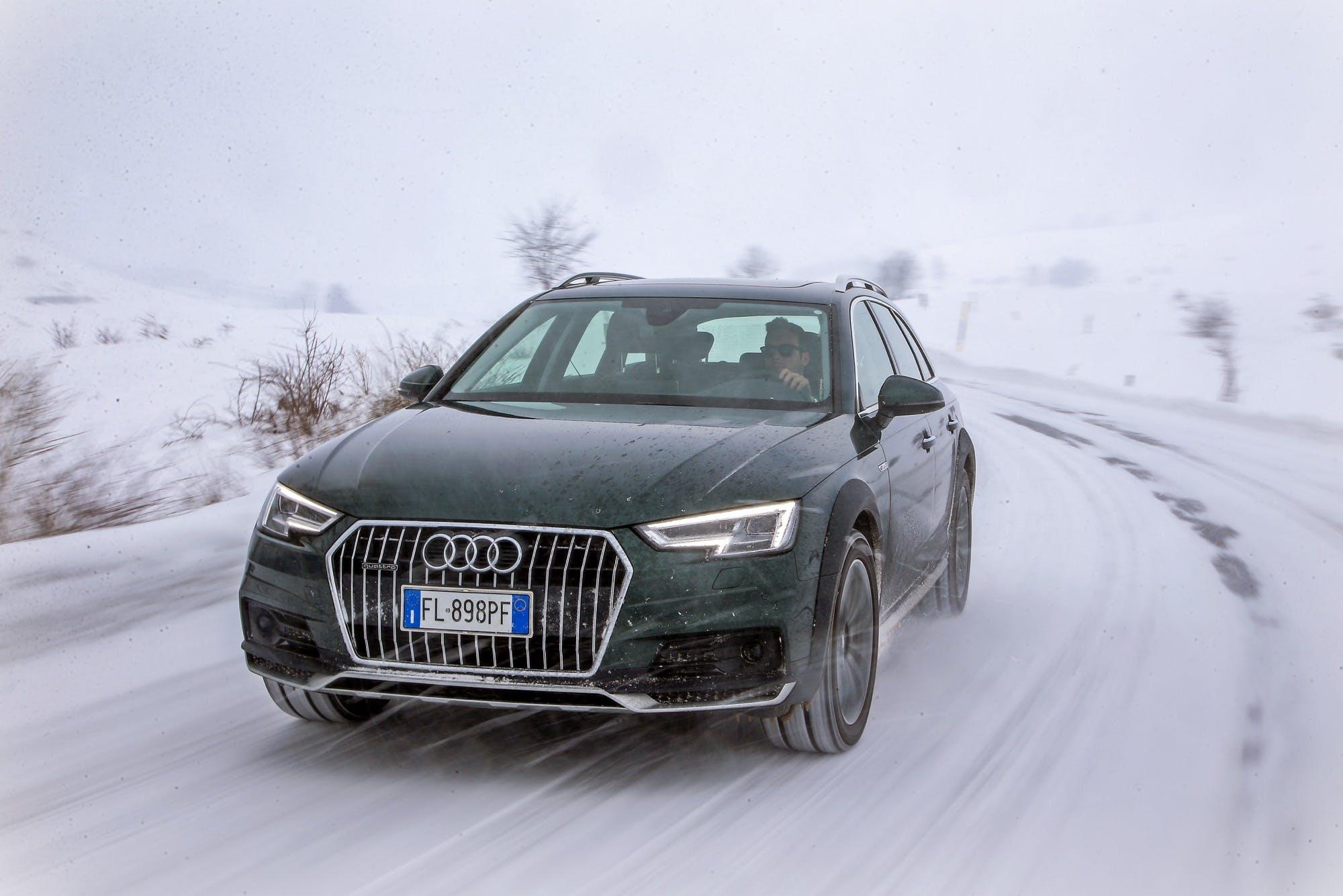 Audi A4 allroad quattro verde percorre una strada di montagna innevata