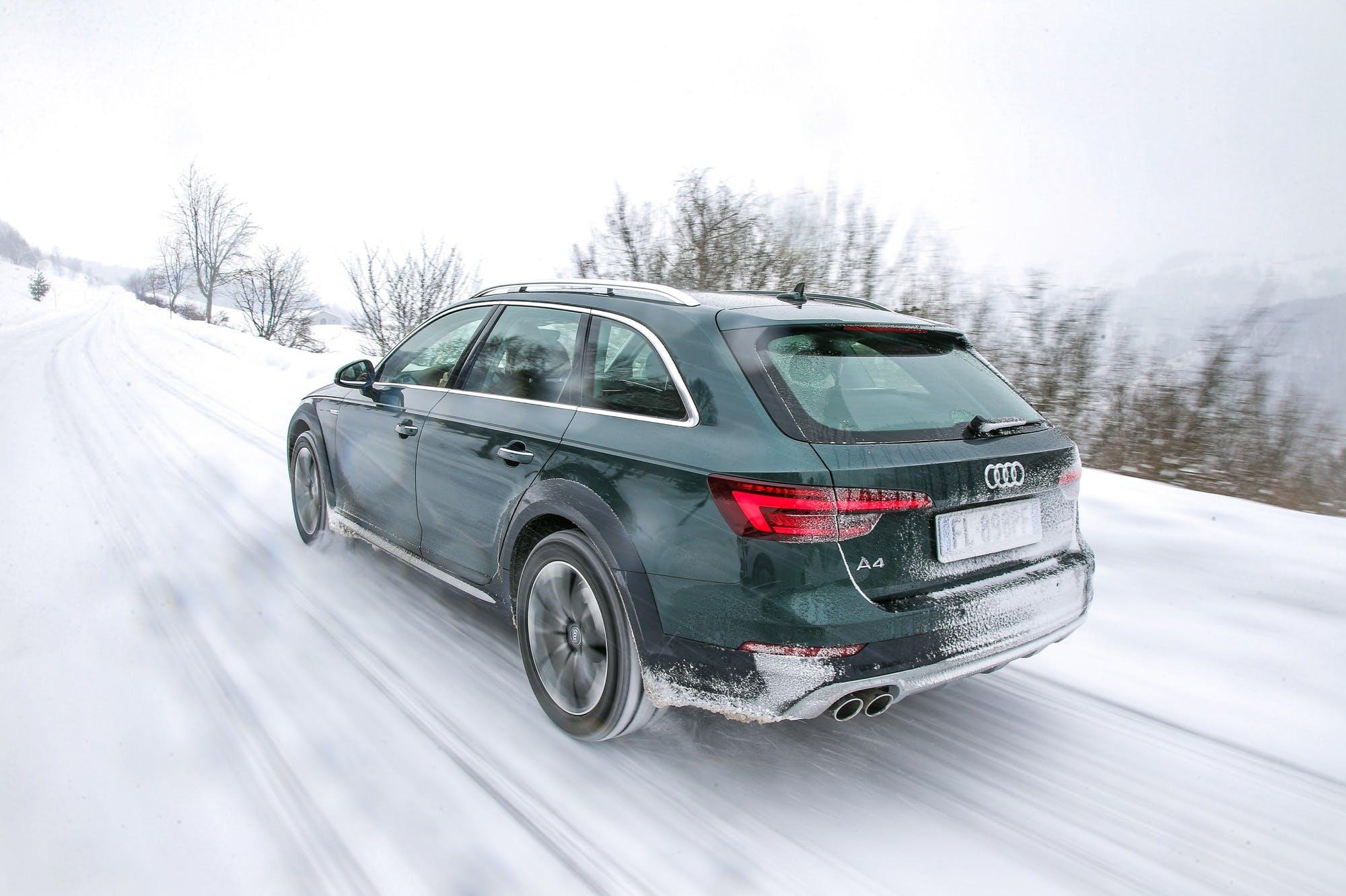 Audi A4 allroad quattro verde vista posteriore dinamica percorre una strada di montagna innevata