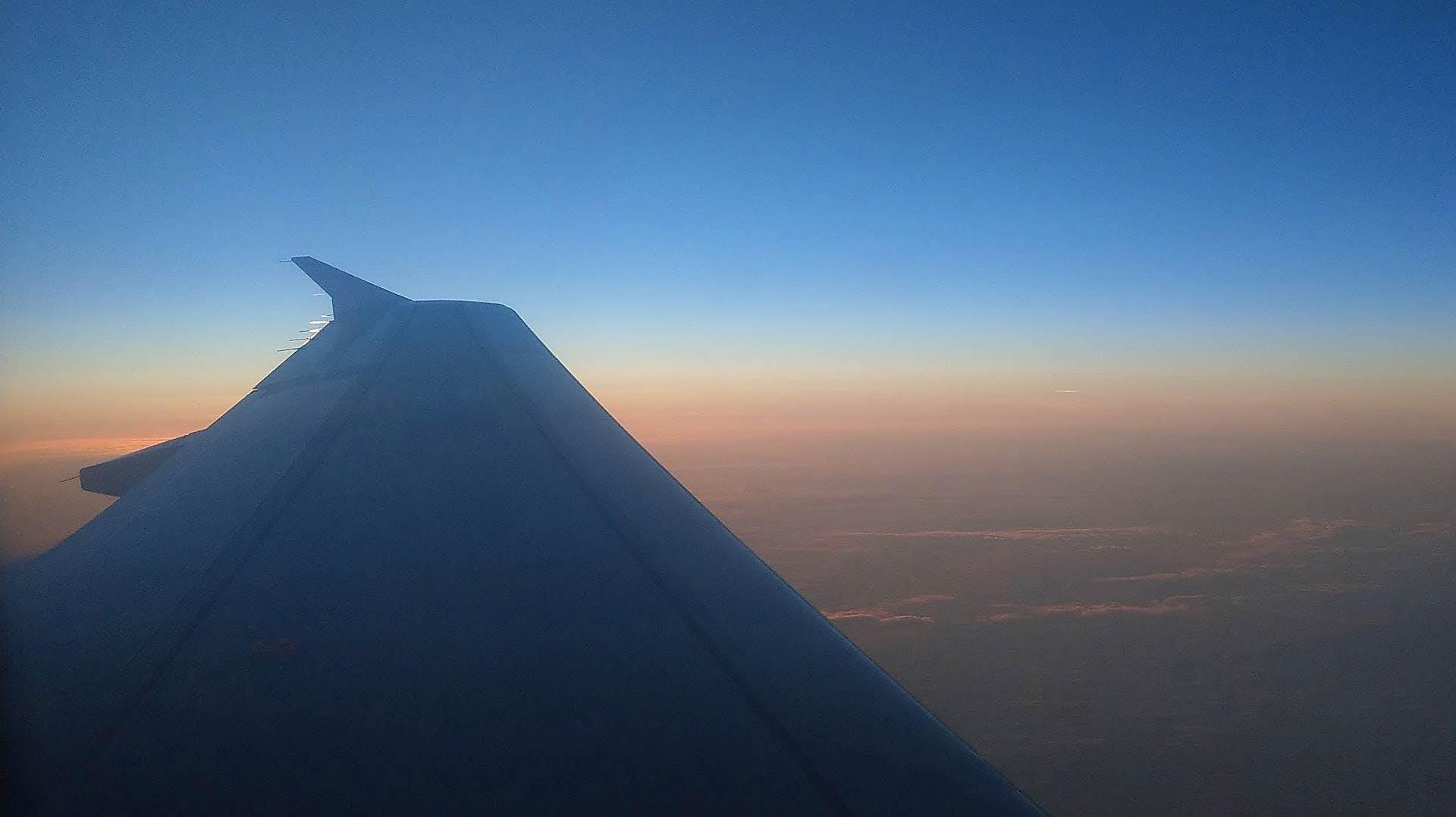 In volo si apprezza lo spettacolare cielo colorato dal tramonto rosso arancio con sfumature verdi