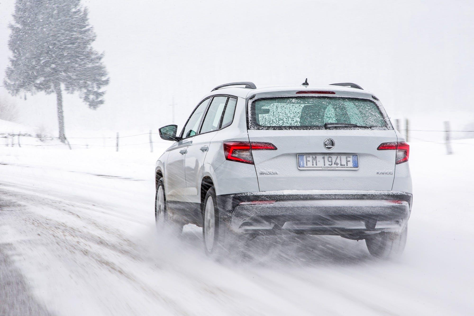 Skoda Karoq bianca vista posteriore avvolta dalla neve in sospensione