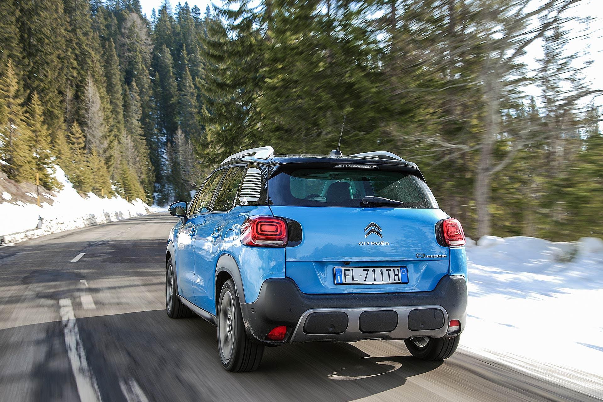 Citroën C3 Aircross azzurra vista posteriore su strada di montagna con neve e pini