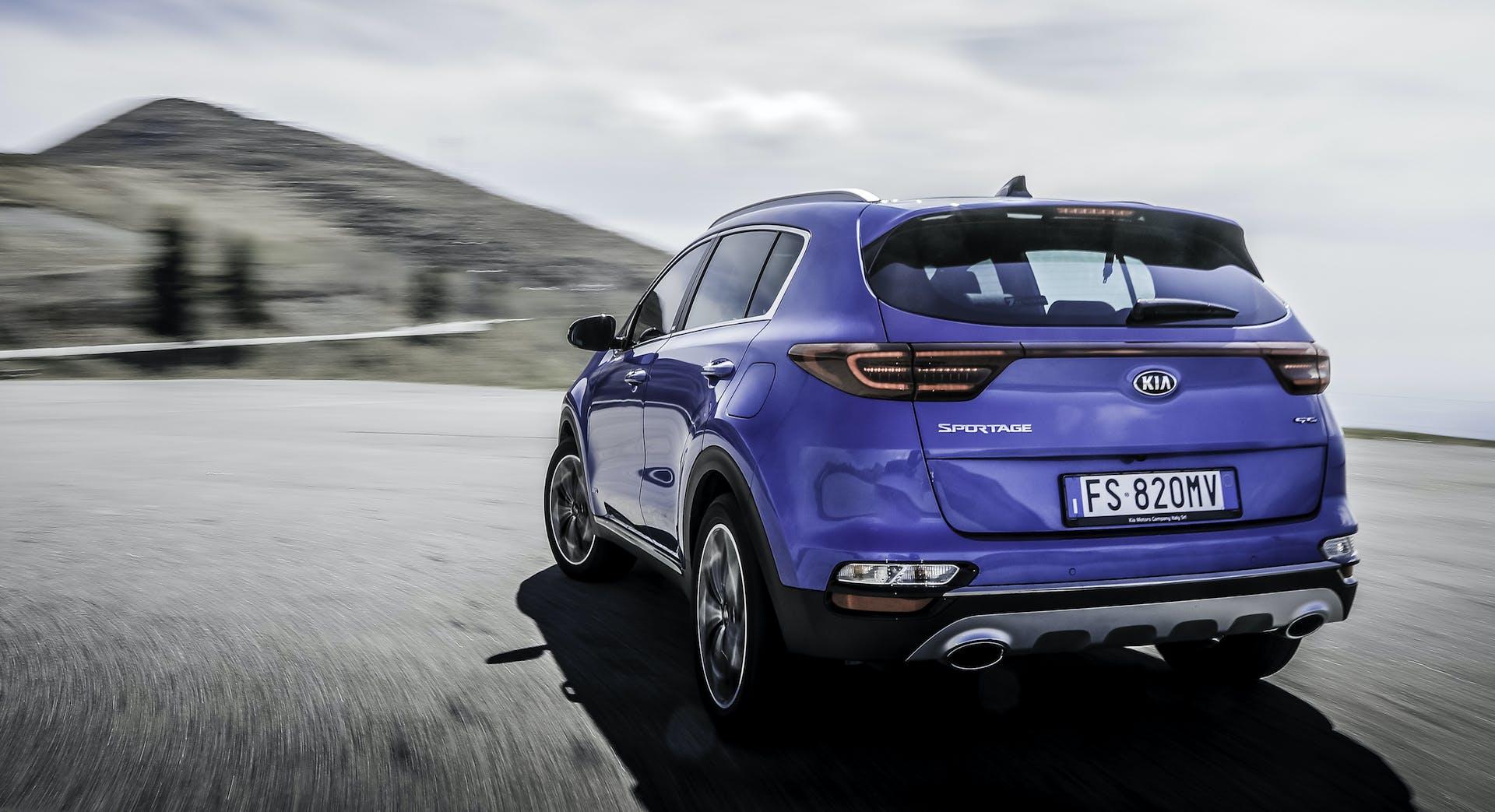 Kia Sportage Hybrid Blu su strada vista tre quarti posteriore
