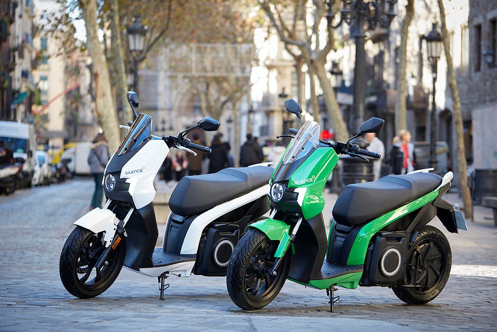 Scooter elettrico Silence S01, vista laterale statica in città, due modelli bianco e verde