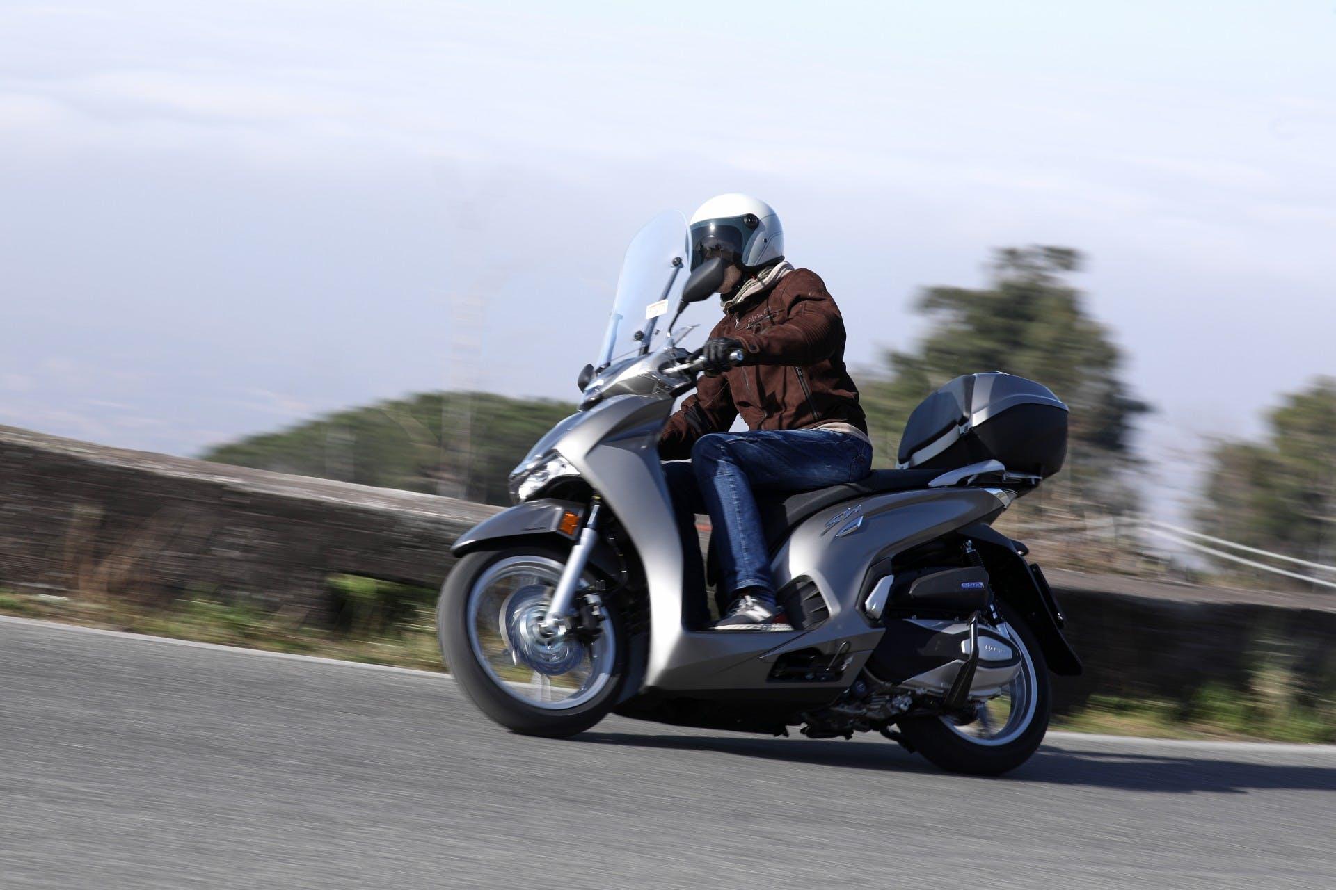 Honda SH 350 grigio in movimento su strada di montagna