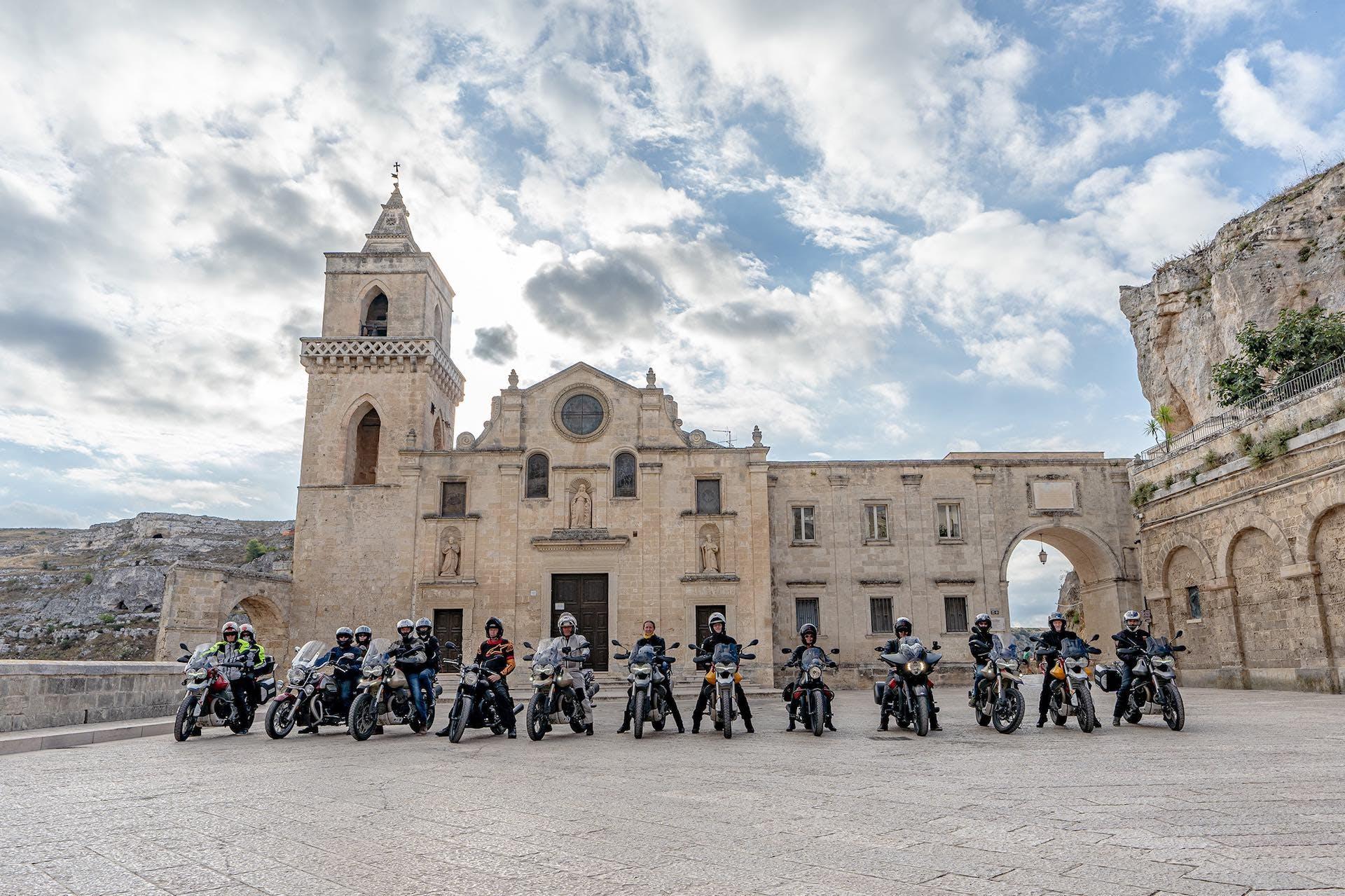 Foto panoramico di motociclisti, partecipanti al Moto Guzzi Experience, parcheggiati in posa una piazza con chiesa sullo sfondo.