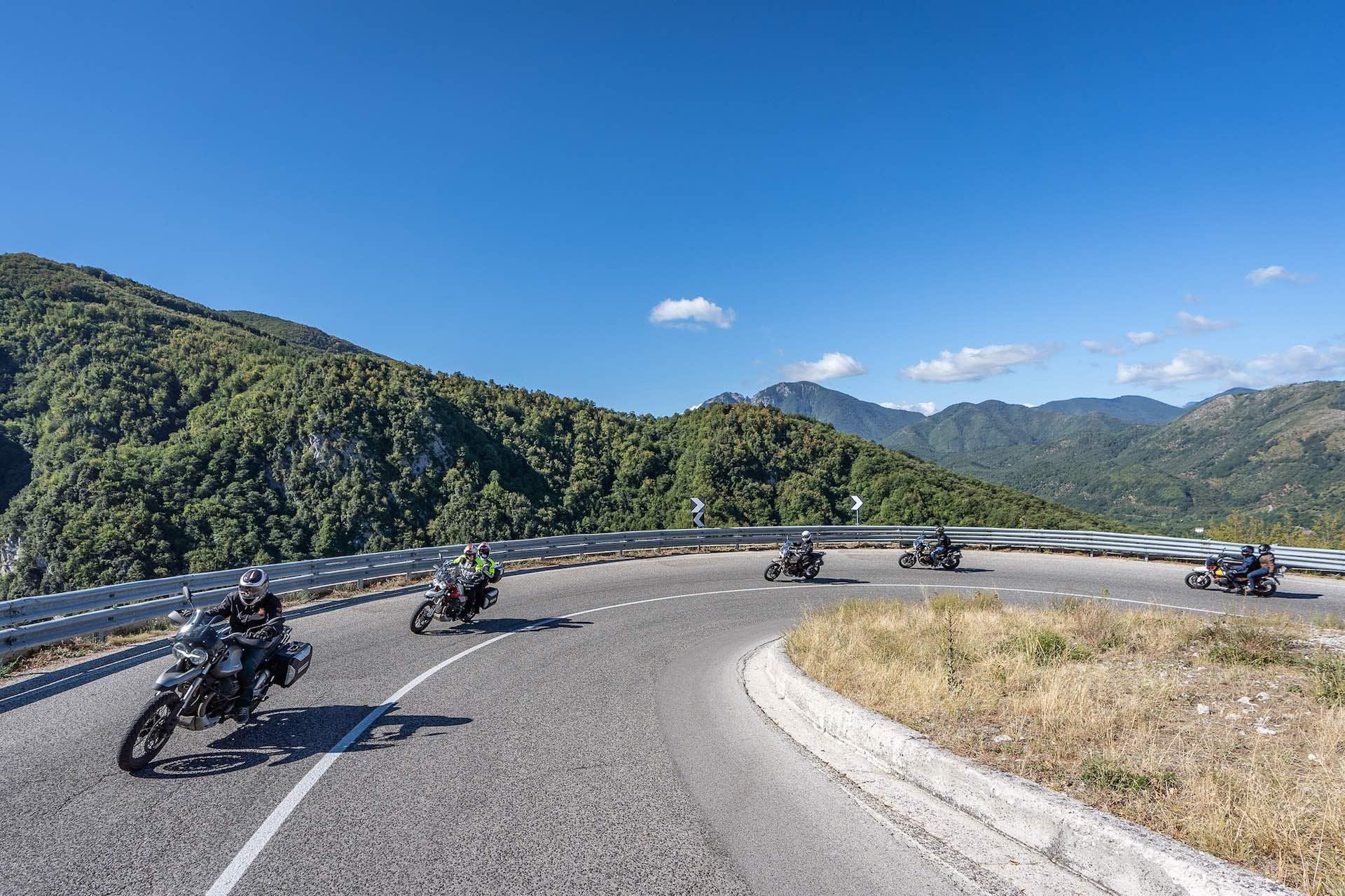 Motociclisti in piega lungo le curve delle tappe del Moto Guzzi Experience.