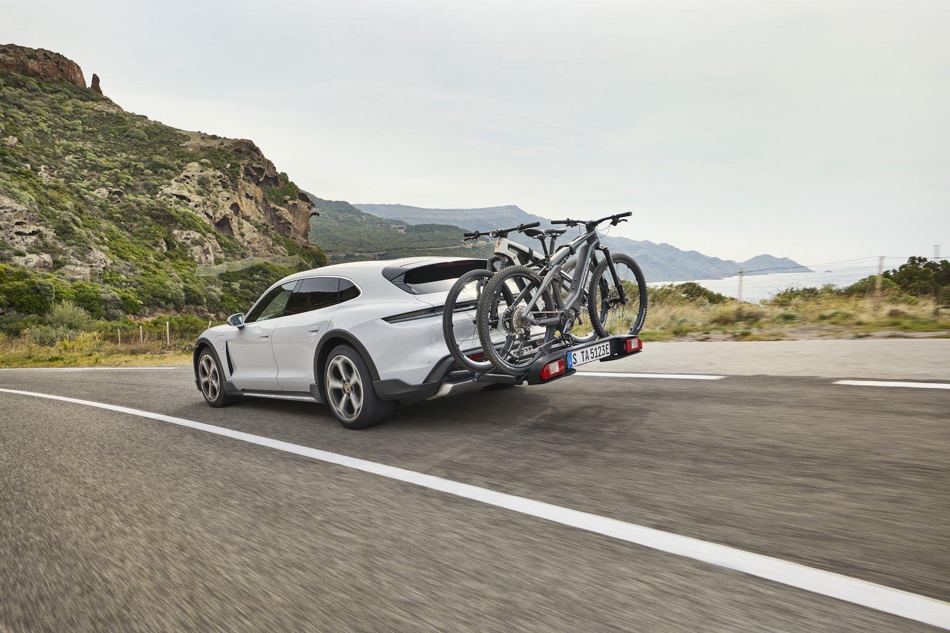Porsche Taycan 4S Cross Turismo in movimento su strada asfaltata con un focus sul portellone posteriore su cui sono agganciate due biciclette elettriche Porsche.