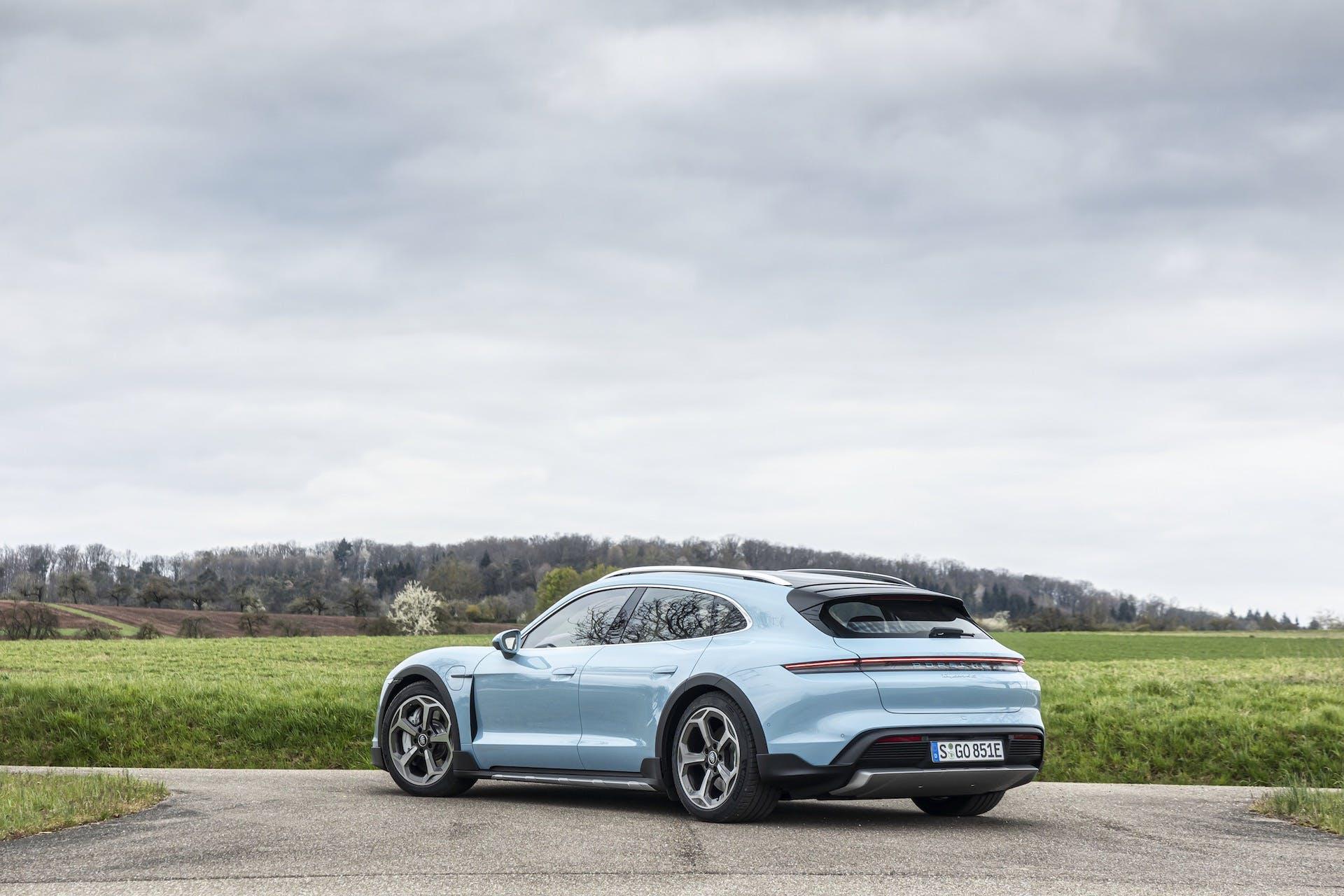 Panoramica laterale posteriore su strada della Porsche Taycan 4S Cross Turismo in colorazione azzurro cielo