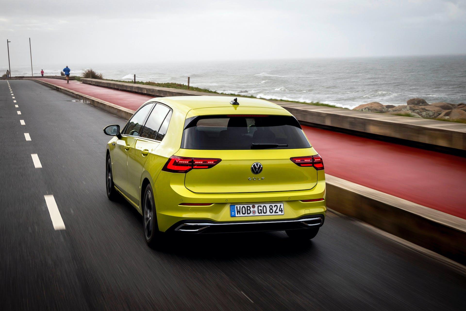 Nuova Volkswagen Golf 8 colo oro su strada con il mare sullo sfondo