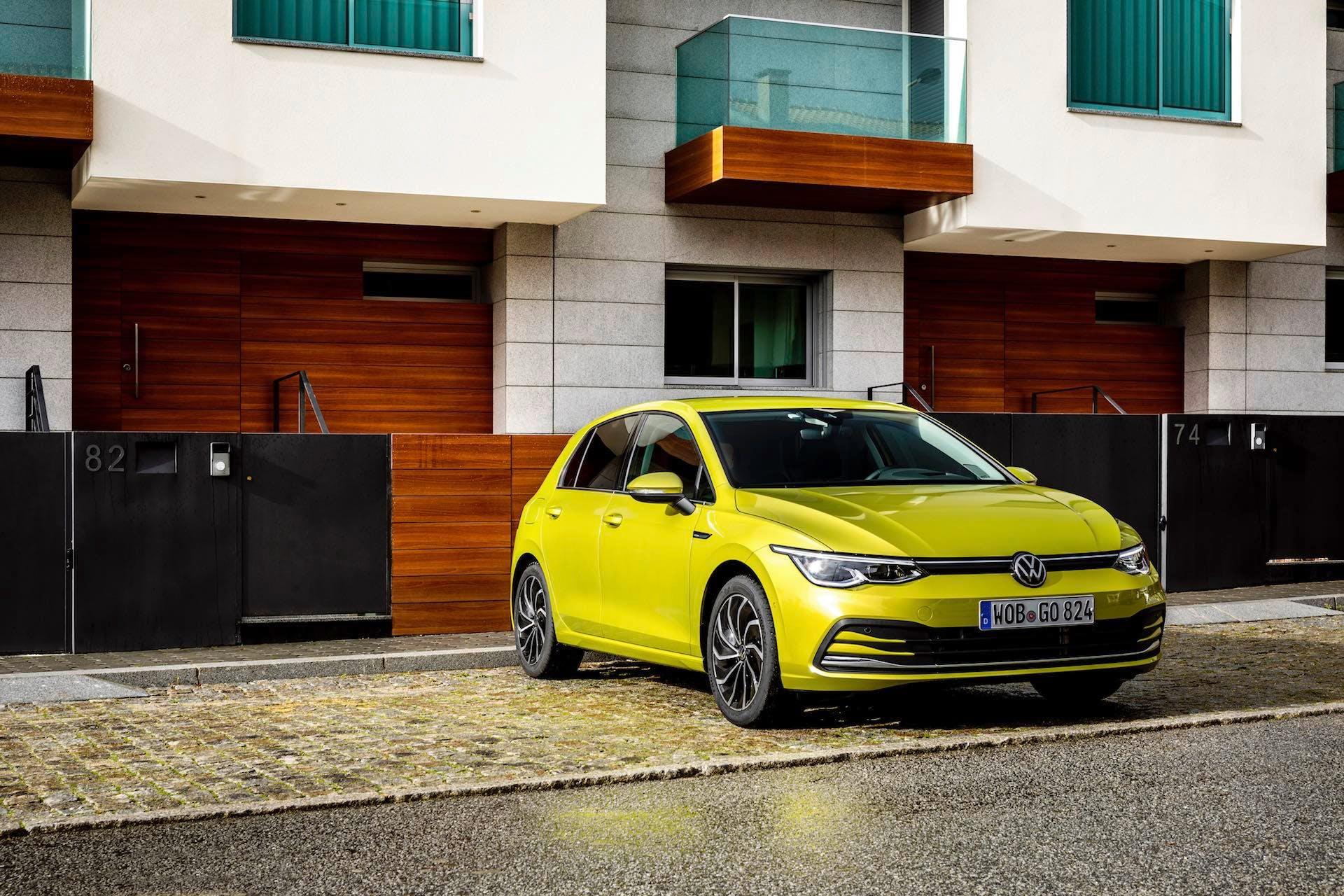 Nuova Volkswagen Golf color oro, parcheggiata ed illuminata dal sole con un edificio come sfondo.