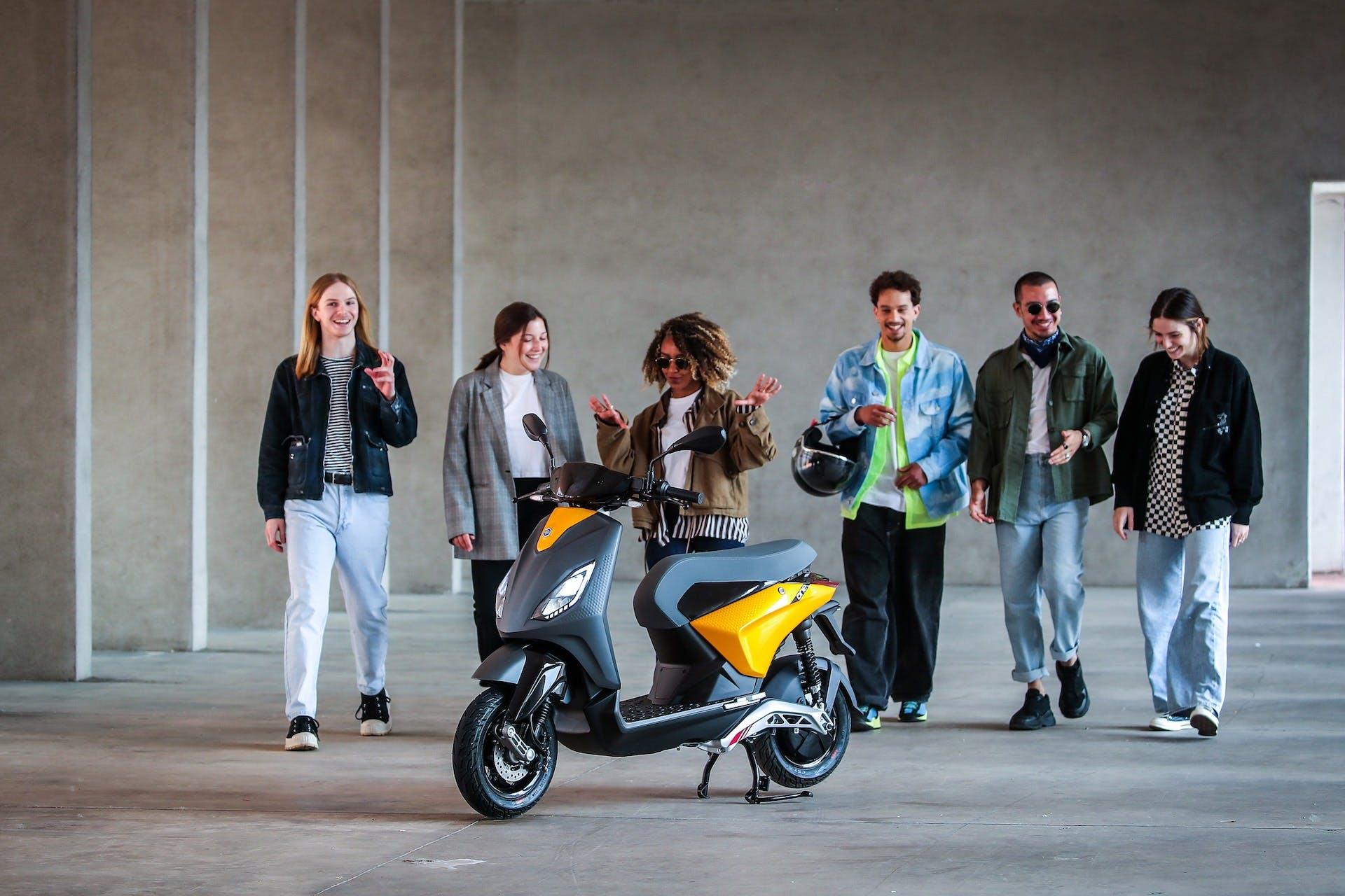 Scooter elettrico Piaggio One fermo su cavalletto e circondato da ragazze e ragazzi