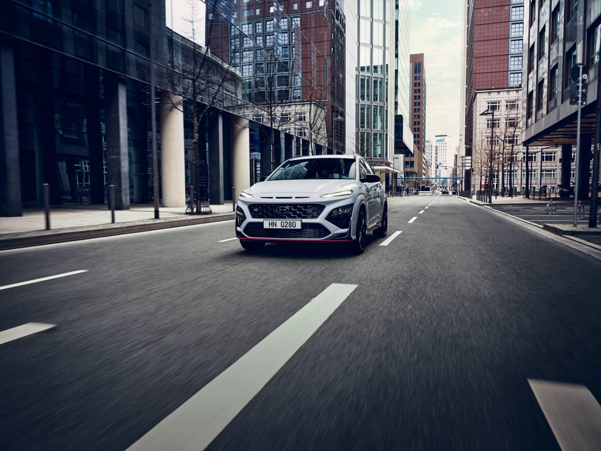 Hyundai Kona N Line vista dall'anteriore mentre percorre una strada asfaltata in ambiente urbano.