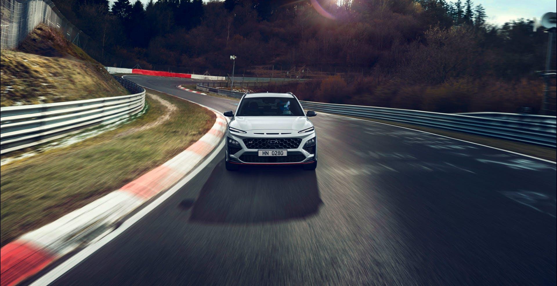 Vista frontale di Hyundai Kona N Line mentre percorre una leggera curva di un circuito
