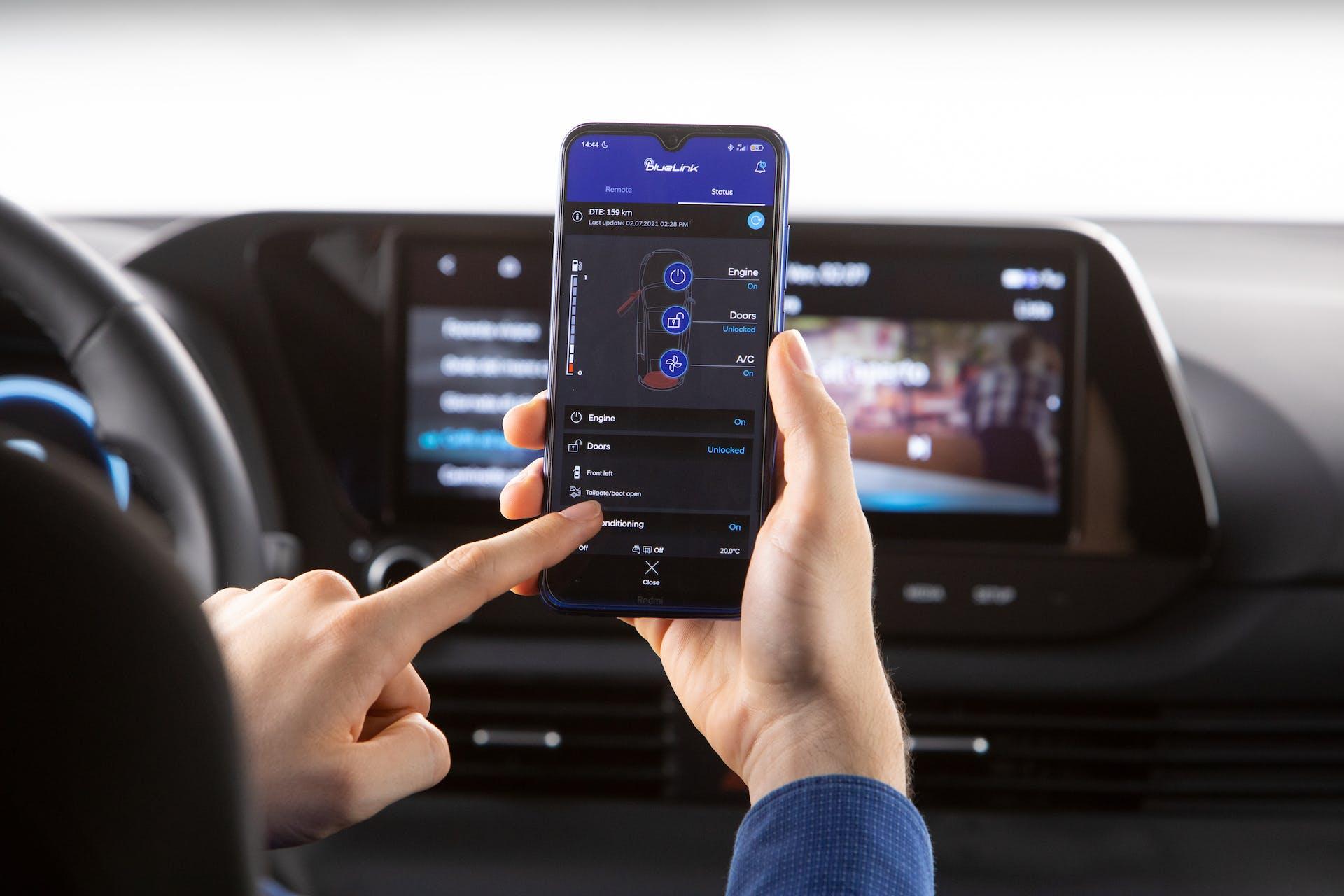 Passegero a bordo di Hyundai Bayon mentre utilizza l'app Blue Link tramite smartphone